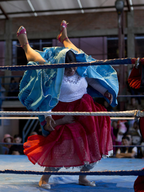 """Cholita wrestler Natalia la Pepita, 19, lifts her trainer Reyna Torrez, 29, as they compete in the ring in El Alto, Bolivia, Monday, January 21, 2019. """"You need a lot of bravery, strength and training to make a good fight. We fall and we hurt, but that doesn't matter because the public has fun"""", said fighter in training Natalia Pepita, whose real name is Noelia Gonzalez. (Photo by Juan Karita/AP Photo)"""