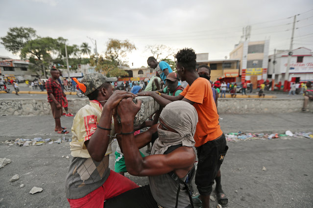 Demonstrators move a lamp post to block a street during anti-government protests in Port-au-Prince, February 15, 2019. (Photo by Ivan Alvarado/Reuters)