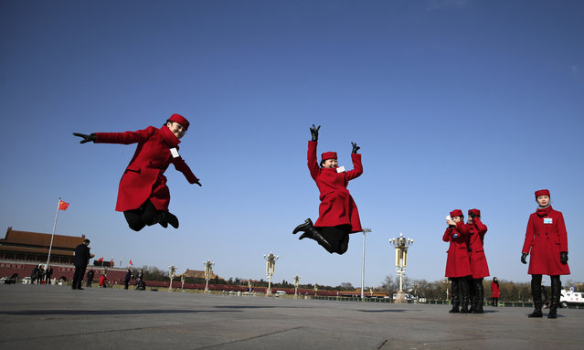 Chinese hostesses, who serve the delegates of the National People's Congress, jump as they pose for photographs on Tiananmen Square during a plenary session of the National People's Congress held at the Great Hall of the People in Beijing, Wednesday, March 9, 2016. (Photo by Andy Wong/AP Photo)
