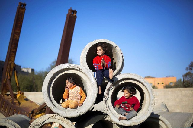 Palestinian children play with concrete pipes in Gaza City, on January 28, 2014. (Photo by Mohammed Abed/AFP Photo)