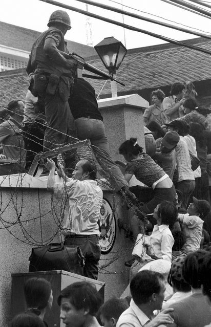 In this April 29, 1975 file photo, people try to scale the 14-foot wall of the U.S. embassy in Saigon, trying to reach evacuation helicopters, as the last of the Americans depart from Vietnam. (Photo by Neal Ulevich/AP Photo)