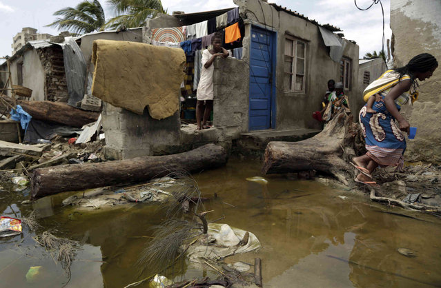 """A woman carrying a baby on her back jumps as she tries to avoid stepping on the dirty water in Beira, Mozambique, Wednesday, March 27, 2019. Cyclone-ravaged Mozambique faces a """"second disaster"""" from cholera and other diseases, the World Health Organization warned on Tuesday, while relief operations pressed into rural areas where an unknown number of people remain without aid more than 10 days after the storm. (Photo by Themba Hadebe/AP Photo)"""