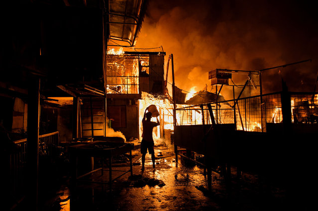 A resident pours water on a fire as it destroys hundreds of houses at an informal settlers community in Delpan, Tondo, Manila on February 7, 2017. (Photo by Noel Celis/AFP Photo)