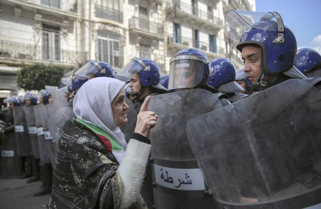 "An elderly woman confronts security forces during a demonstration in Algiers, Algeria, Wednesday, April 10, 2019. The Algerian senator Abdelkader Bensalah named to temporarily fill the office vacated by former President Abdelaziz Bouteflika said he would act quickly to arrange an ""honest and transparent"" election to usher in an ""Algeria of the future"". (Photo by Mosa'ab Elshamy/AP Photo)"