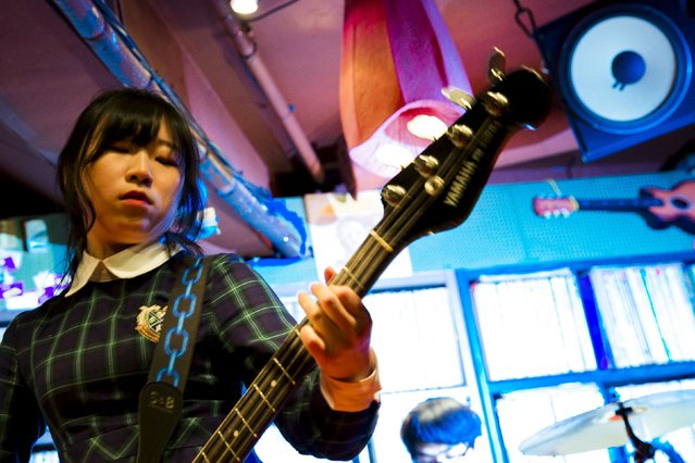 A woman plays the bass guitar during a punk rock concert in a small basement club in the trendy nightlife district of Hongdae in Seoul, May 2, 2015. (Photo by Thomas Peter/Reuters)