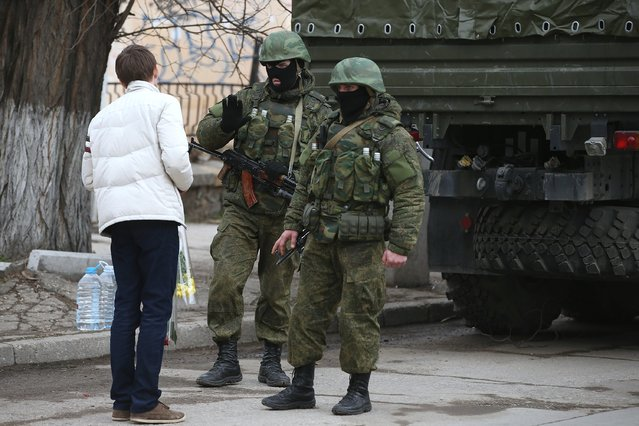A young man carrying flowers confronts heavily-armed soldiers displaying no identifying insignia in a street in the city center on March 1, 2014 in Simferopol, Ukraine. (Photo by Sean Gallup/Getty Images)