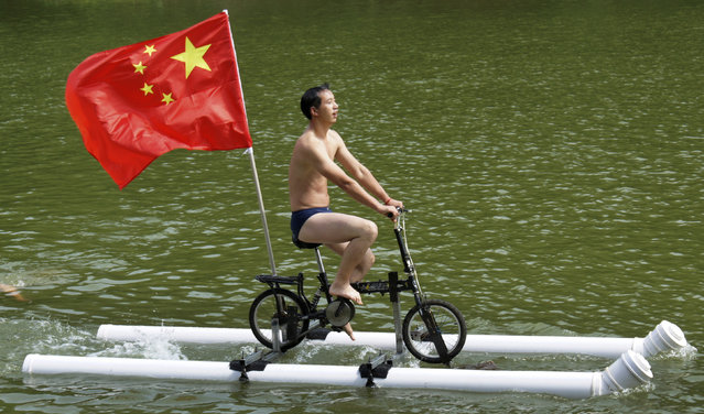 A Chinese flag is seen as Liu Wanyong performs on his invention, an improvised bicycle which is held afloat by plastic tubes, in Zhenning, Guizhou province, August 29, 2013. (Photo by Reuters/Stringer)