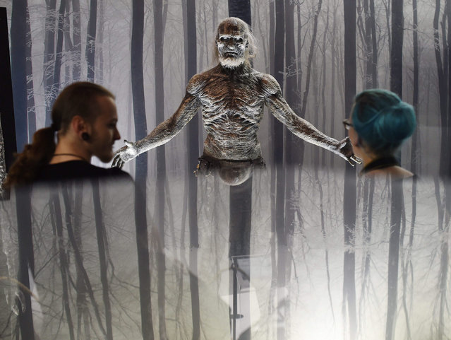 """Two visitors look at the figure of a character, from the US-series """"Game of Thrones"""", a white walker, mirrored on the surface of a window, is on display during the openinig of the """"Game of Thrones"""" exhibition in Berlin, Germany, 13 May 2015. The exhibition runs from 13 May to 17 May. (Photo by Jens Kalaene/EPA)"""
