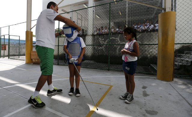 """A fencing instructor helps a child from municipal school Parana during the project """"Fencing School"""" in Rio de Janeiro, Brazil, March 30, 2016. (Photo by Sergio Moraes/Reuters)"""