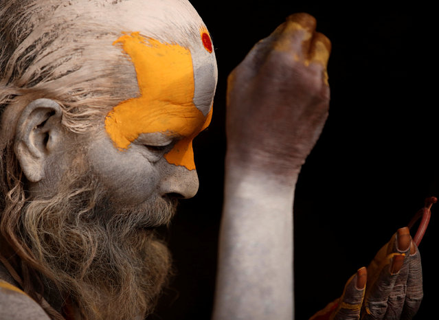 A Hindu holy man, or sadhu, smeared with ashes applies tika on his forehead at the premises of Pashupatinath Temple, ahead of the Shivaratri festival in Kathmandu, Nepal February 21, 2017. (Photo by Navesh Chitrakar/Reuters)