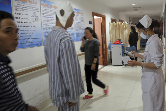 A brain surgery patient walks down the main corridor of Ruijin Hospital's functional neurosurgery center in Shanghai, China on Monday, Oct. 29, 2018. Doctors at Ruijin are experimenting with brain surgery to treat a range of psychiatric conditions, including anorexia, Tourette syndrome and addiction. (Photo by Erika Kinetz/AP Photo)