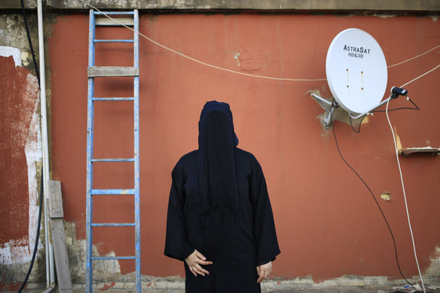 This Friday, May 1, 2015 shows a 32-year old Lebanese woman, whose father is a Shiite Muslim and mother is a Sunni Muslim, posing for a photograph, on the roof of her home in Beirut, Lebanon. For most, the niqab is a choice. They do so out of their own interpretation of the Quran and the hadith, a collection of traditions and anecdotes about the Prophet Muhammad, believing that a woman's body should be covered out of modesty. (Photo by Hassan Ammar/AP Photo)