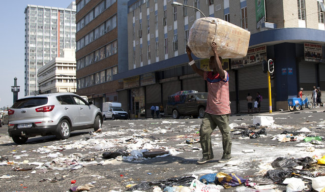 A pedestrian crosses an intersection littered with uncollected refuse, in Johannesburg, South Africa, Monday, April 4, 2016, as some thousands of garbage collectors have been on strike since March 9. Some streets in Johannesburg resemble a dumping site, with pedestrians stepping over piles of refuse and motorists battled for alternative routes as some roads have become impassable. (Photo by Themba Hadebe/AP Photo)