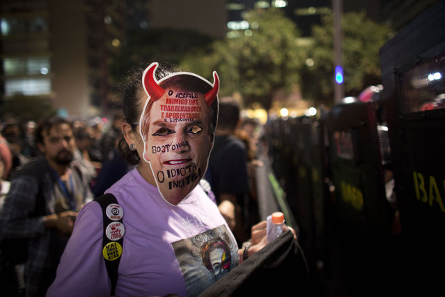 A woman wears a retouched mask with the image of Brazil's President Jair Bolsonaro during a protest against education cuts in Sao Paulo, Brazil, Thursday, May 23, 2019. A few hundred students demonstrated in Rio de Janeiro and Sao Paulo to protest big cuts in federal funding for the public education network by President Jair Bolsonaro. (Photo by Victor R. Caivano/AP Photo)