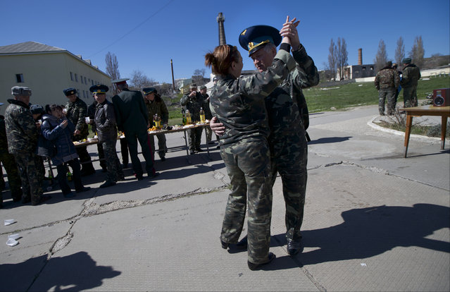 Ukrainian airmen dance as they celebrate their comrade's wedding at the Belbek airbase outside Sevastopol, Crimea, on Saturday, March 22, 2014. Two young Lieutenants, medic Galina Volosyanchik and communication officer Ivan Benera got married today and arrived to their unit for a short celebration as Russian troops continue to occupy part of the airbase and demand surrender of Ukrainian airmen. (Photo by Ivan Sekretarev/AP Photo)