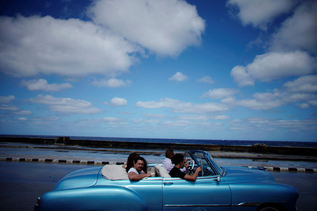 Tourists ride in a vintage car at the seafront Malecon in Havana, Cuba, March 6, 2019. (Photo by Alexandre Meneghini/Reuters)