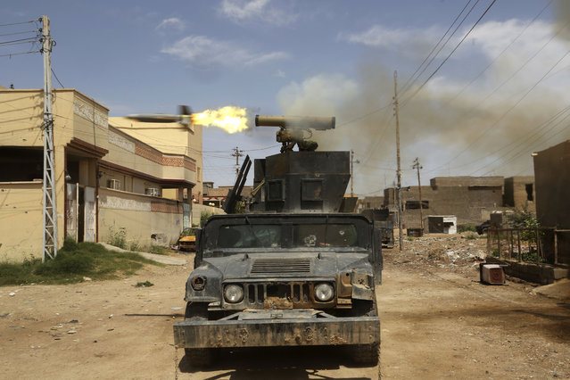 Iraq's elite counterterrorism forces fire towards extremist positions during fights between Iraqi security forces and Islamic State group during a military operation to regain control of Hit, 85 miles (140 kilometers) west of Baghdad, Iraq, Wednesday, April 13, 2016. (Photo by Khalid Mohammed/AP Photo)