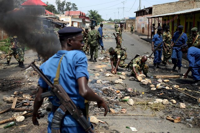 Policemen and soldiers clear a barricade during a protest against President Pierre Nkurunziza and his bid for a third term in Bujumbura, Burundi, May 25, 2015. (Photo by Goran Tomasevic/Reuters)