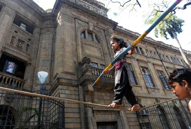 This photo taken on February 7, 2014 shows nine-year-old Indian girl Barsati walking on a tightrope entertaining a crowd of onlookers in Mumbai. Barsati spends just a few weeks each year going to school during India's rainy season, according to her uncle, but the rest of her time is spent earning for her family. She is one of more than 28 million Indian children estimated by UNICEF to be engaged in some form of labour. (Photo by Indranil Mukherjee/AFP Photo)