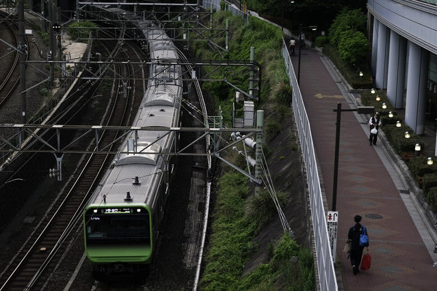 In this Wednesday, May 22, 2019, photo, a Yamanote Line train departs from Ikebukuro Station in Tokyo. Operated by the East Japan Railway Co., the Yamanote Line in Tokyo makes a loop around the center of the city, connecting 29 stations that include key stops such as Shinjuku, Shibuya and Ikebukuro. A complete loop of about an hour offers scenes of Japanese daily lives: jam-packed morning commute, views of the famous Shibuya crossing, high-rises, downtown shopping arcades, and a quick break at a noodle stand. (Photo by Jae C. Hong/AP Photo)