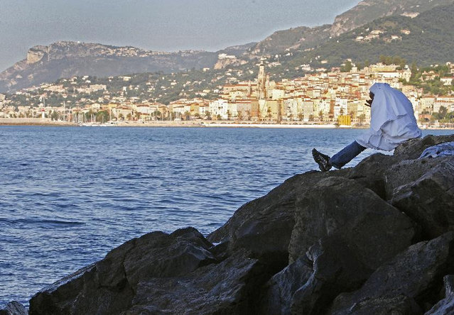 A migrant sits on the rocky beach at the Franco-Italian border near Menton, southeastern France Wednesday, June 17, 2015. European Union nations failed to bridge differences Tuesday over an emergency plan to share the burden of the thousands of refugees crossing the Mediterranean Sea, while on the French-Italian border, police in riot gear forcibly removed dozens of migrants. (AP Photo/Lionel Cironneau)