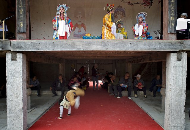 Performers play local opera on stage while people sit and a boy plays under the stage in Wanrong county, Shanxi Province, China, April 24, 2016. (Photo by Reuters/China Daily)