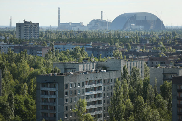 The former Chernobyl nuclear power plant, including destroyed reactor four (C), as well as the New Safe Confinement structure (R) that will one day enclose the remains of reactor four, stand behind the abandoned city of Pripyat on September 30, 2015 near Pripyat, Ukraine. (Photo by Sean Gallup/Getty Images)