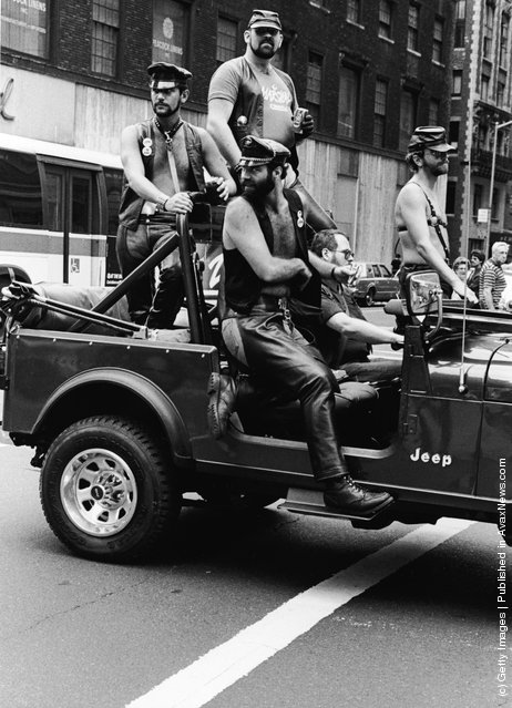 A group of men dressed in leather fetish clothing ride in a truck at the intersection of 32nd Street and Fifth Avenue during the annual Gay Pride parade in New York City, c. 1980