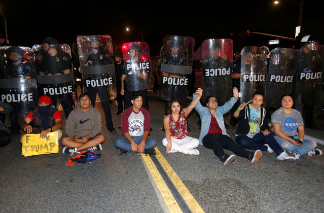 Demonstrators sit in front of a line of police in riot gear outside Republican U.S. presidential candidate Donald Trump's campaign rally in Costa Mesa, California April 28, 2016. (Photo by Mike Blake/Reuters)