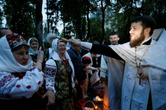 A Ukrainian Orthodox priest sprinkles holy water on believers on the eve of Orthodox Easter service in Kiev, Ukraine, April 30, 2016. (Photo by Valentyn Ogirenko/Reuters)