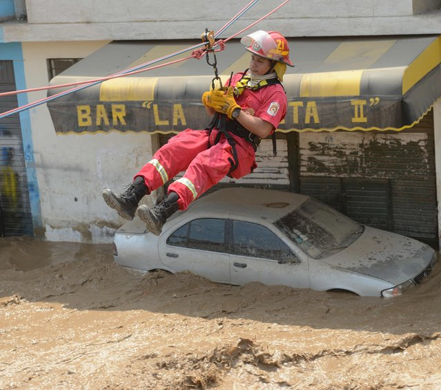 Residents of the Huachipa populous district, east of Lima, are helped on March 17, 2017, by police and fire fighter rescue teams to cross over flash floods hitting their neighbourhood and isolating its residents. (Photo by Cris Bouroncle/AFP Photo)