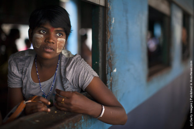 A Burmese woman sits on board a local train waiting for it to depart the Yangon station