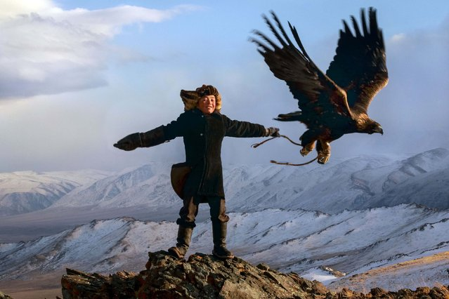 13 year old Irka Bolen with his eagle. Tradition wise, when a boy turns 13, then are strong enough to hold the weight of a fully grown eagle. (Photo by Asher Svidensky/Caters News)