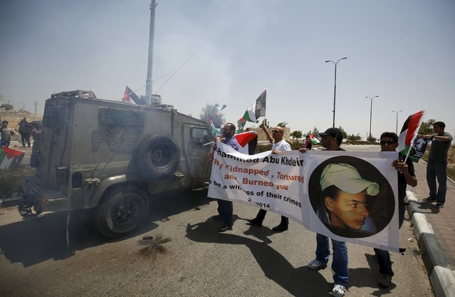 Palestinian protesters standing near an Israeli army jeep hold a banner with a picture of 16-year-old Palestinian Mohammed Abu Khudair, who was burnt in Jerusalem in a suspected revenge attack for the kidnapping and slaying of three Israeli teens last year, during a protest marking the first anniversary of Abu Khudair's killing, near the West Bank city of Ramallah July 2, 2015. (Photo by Mohamad Torokman/Reuters)