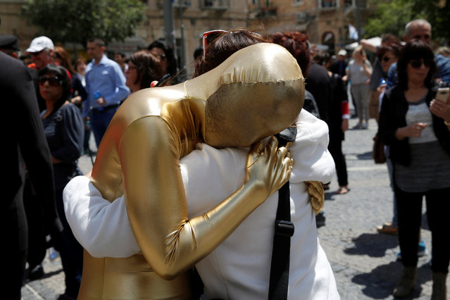 A member of the Prizma Ensemble wearing a full solid-coloured bodysuit hugs a bystander as she takes part in the 6th Jane's Walk Jerusalem in Jerusalem May 6, 2016. (Photo by Baz Ratner/Reuters)