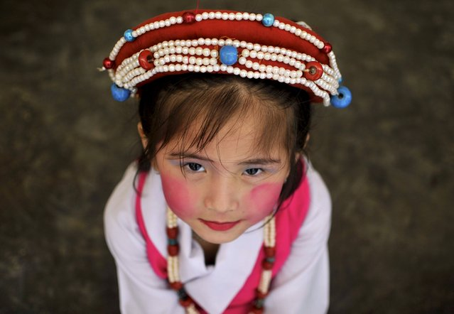 A Tibetan girl in a traditional costume waits backstage before performing at celebrations marking the 80th birthday celebrations of the Tibetan spiritual leader the Dalai Lama, at the Sera Jey Monastery in Bylakuppe in the southern state of Karnataka, India, July 6, 2015. (Photo by Abhishek N. Chinnappa/Reuters)