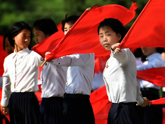 School girls practice flag waving in advance of the upcoming seventh congress for the ruling Workers' Partyt this week in Pyongyang, North Korea on May 4, 2016. The last time the Party met was in 1980 and expectations are high this week that there could be an announcement of changes within the party structure. (Photo by Linda Davidson/The Washington Post)