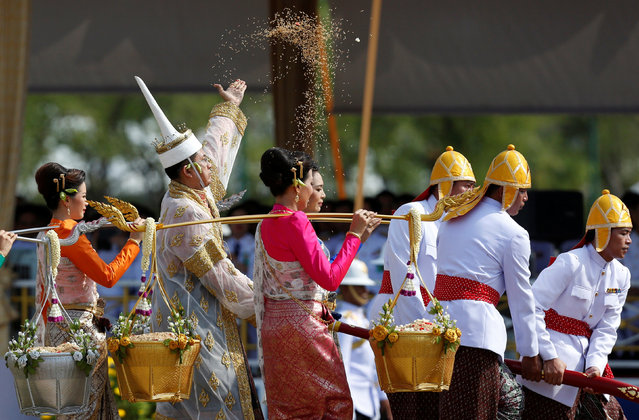 Thai officials dressed in traditional costumes throw rice during the annual royal ploughing ceremony  in central Bangkok, Thailand, May 9, 2016. (Photo by Athit Perawongmetha/Reuters)