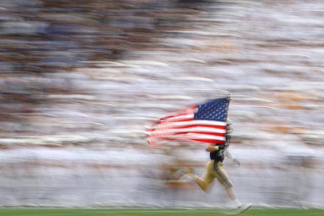 Travis Brannan #22 of the Navy Midshipmen carries the U.S. flag as he and teammates take the field before playing against the East Carolina Pirates during the first half at Navy-Marine Corps Memorial Stadium on September 14, 2019 in Annapolis, Maryland. (Photo by Patrick Smith/Getty Images)