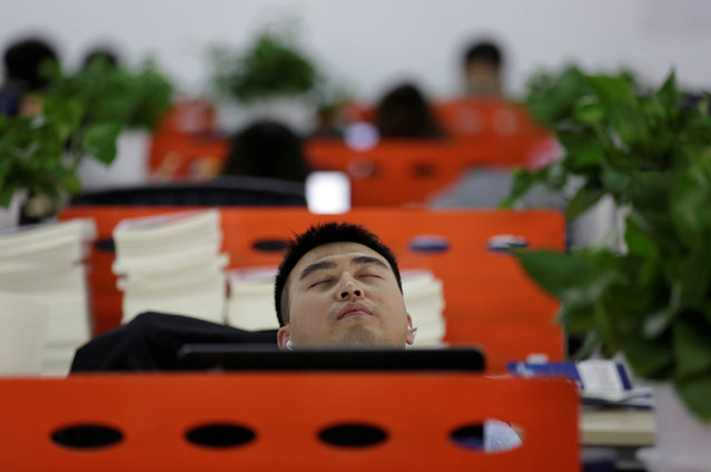 Cui Meng, a Co-founder of Goopal Group, takes a nap in his seat after lunch, in Beijing, China, April 21, 2016. (Photo by Jason Lee/Reuters)