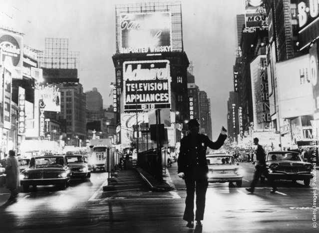 1965: A policeman directs traffic in front of the famous neon billboards of Times Square in New York City, at its intersection with Broadway