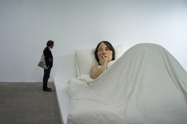 "A visitor looks at the sculpture ""In bed"" by Australian artist Ron Mueck on display during the exhibition ""Vivid Memories"" at the Fondation Cartier Museum in Paris, France, 09 May 2014. The exhibition celebrates the 30th anniversary of the Cartier Foundation by focusing on the works the museum has collected since 1984. The exhibition runs from 10 May to 21 September 2014. (Photo by Yoan Valat/EPA)"