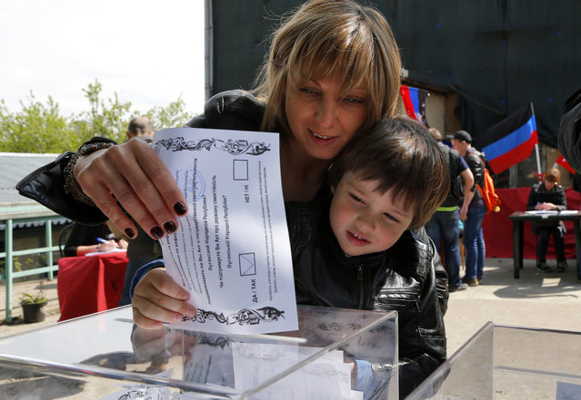 An Ukrainian woman and her son, who are in Russia at the moment, cast a referendum ballot in Moscow, Russia, on Sunday, May 11, 2014. Residents of two restive regions in eastern Ukraine cast ballots Sunday in referendums, which seek approval for declaring sovereign people's republics in the Donetsk and Luhansk regions. Many of Ukrainians living in Moscow came to vote as well. (Photo by Dmitry Lovetsky/AP Photo)