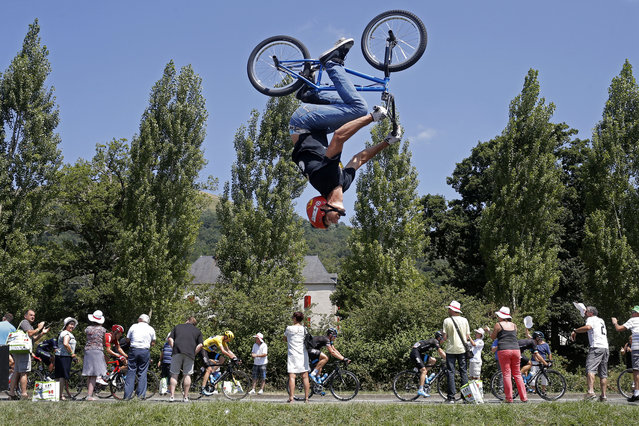 A man performs a BMX bike stunt as the pack with Britain's Christopher Froome, wearing the overall leader's yellow jersey, passes during the tenth stage of the Tour de France cycling race over 167 kilometers (103.8 miles) with start in Tarbes and finish in La Pierre-Saint-Martin, France, Tuesday, July 14, 2015. (Photo by Laurent Cipriani/AP Photo)