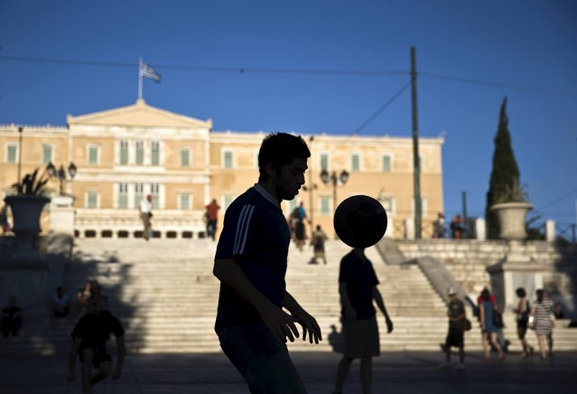 A street performer plays with a ball at the Constitution (Syntagma) square near the Parliament building in Athens, Greece July 18, 2015. The Greek government ordered banks to open on Monday, three weeks after they were shut down to prevent the system collapsing under a flood of withdrawals, as Prime Minister Alexis Tsipras looked to the start of new bailout talks next week. (Photo by Ronen Zvulun/Reuters)