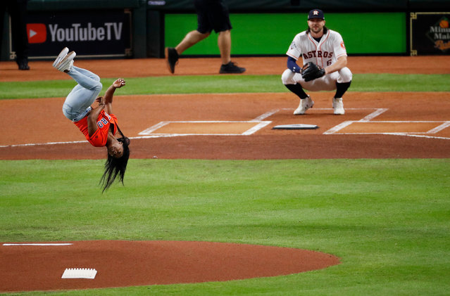 Gymnast Simone Biles performs a flip after throwing out the ceremonial first pitch prior to Game Two of the 2019 World Series between the Houston Astros and the Washington Nationals at Minute Maid Park on October 23, 2019 in Houston, Texas. (Photo by Tim Warner/Getty Images)