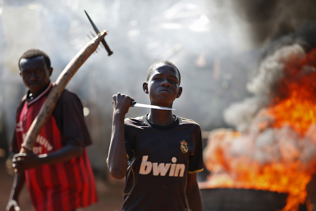 A boy gestures in front of a barricade on fire during a protest after French troops opened fire at protesters blocking a road in Bambari May 22, 2014. (Photo by Goran Tomasevic/Reuters)