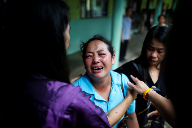 Malawian Saw-wa, 33, who lost her daughter, cries near a burnt building at the Pitakkiat Wittaya School in the northern province of Chiang Rai, Thailand, May 23, 2016. (Photo by Athit Perawongmetha/Reuters)