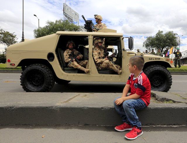 A boy watches as soldiers pass by in a military vehicle during Colombia's Independence Day parade in Bogota, Colombia July 20, 2015. Colombia commemorates the 205th anniversary of its independence from Spain on Monday. (Photo by Jose Miguel Gomez/Reuters)
