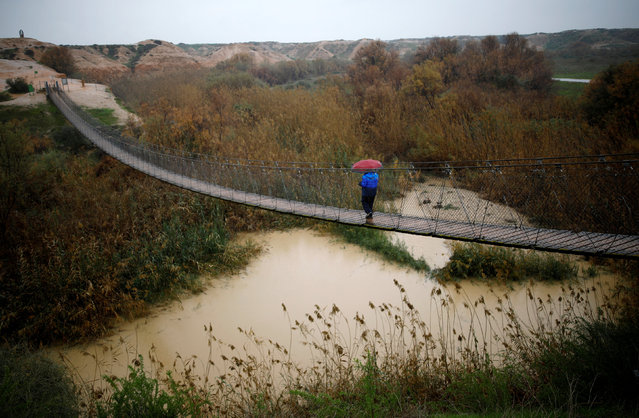 A man walks on a bridge crossing over the Besor stream on a rainy day, near Kibbutz Tze'elim in Israel's southern Negev desert February 16, 2017. (Photo by Amir Cohen/Reuters)